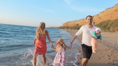 Happy family walks along the seashore in slow motion — Wideo stockowe