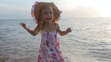 Little cute girl in sundress and straw hat standing knee-deep in sea water — Stok video