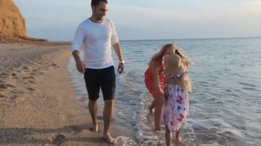 Little carefree girl running along the beach to the parents in slow motion — Vidéo