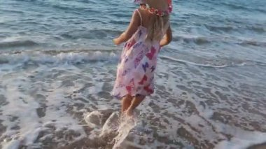 Little girl full of emotions walking along the seashore with her parents in slow motion — Wideo stockowe