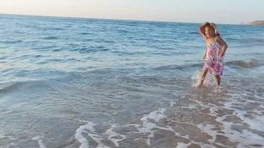 Little happy girl running along the seashore to her parents in slow motion — Stock Video