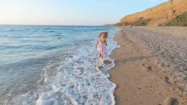 Little girl running along the sea to her parents leaving footprints on the sand — Wideo stockowe