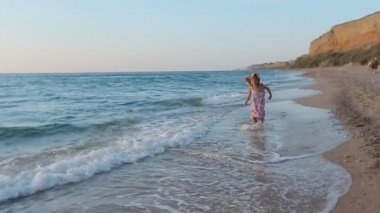 Little girl in sundress running along the sea to father and he lifts her up in slow motion — Stok video