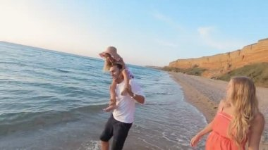 Happy family fooling around while walking along the seashore — Wideo stockowe