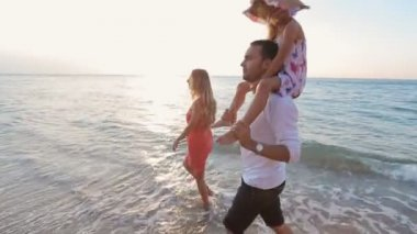 Happy family walking along the beach barefoot — Wideo stockowe