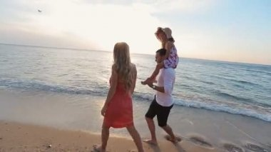Friendly family walking along the beach and leaving footprints in the sand — Wideo stockowe