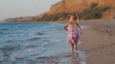 Little girl runing along the beach in sundress in slow motion back view — Stock Video