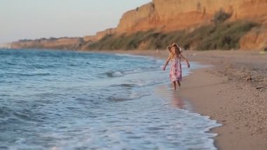 Little girl in sundress and hat running along the beach in slow motion — Vidéo