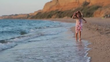 Little girl running along the beach leaving footprints in the sand in slow motion — Stock Video