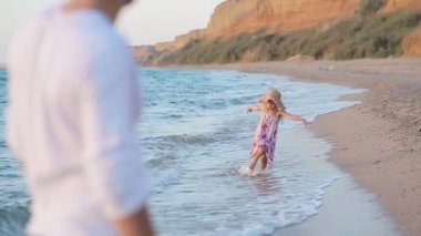 Little girl running along the beach to her father in slow motion — Stock Video