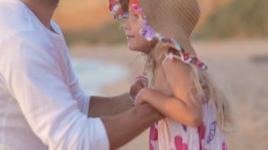 Father picks up little girl in hat on sea in slow motion — Stock Video