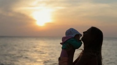 Silhouette of mother kissing baby at sunset near the sea in slow motion — Vídeo de stock