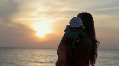 Silhouette of mother holding toddler on hands at sunset near the sea in slow motion — Stock Video