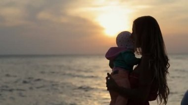 Silhouette of mother kissing baby at sunset near the sea — Stockvideo