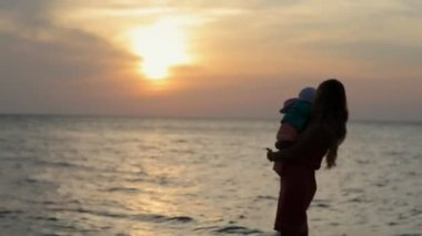 Silhouette of mother holding baby while standing near sea at sunset — Stock Video