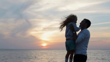 Father throws up in the air little happy girl near the sea in slow motion — Stock Video