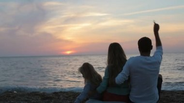 Happy family sitting in the sunset near the sea in slow motion — Stock Video