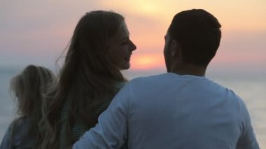 Family sitting near the sea at sunset, the husband and wife hugging in slow motion — Stock Video