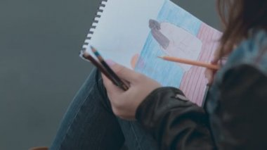 Dreamy girl painting a picture with pencils sitting at berth — Stock Video