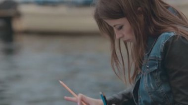 Talented girl painting a picture with colored pencils while sitting near the sea at berth — Stock Video