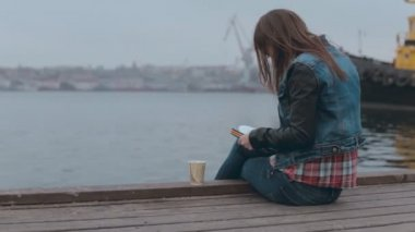 Absorbed in drawing girl sitting on a wooden pier near the sea — Stockvideo