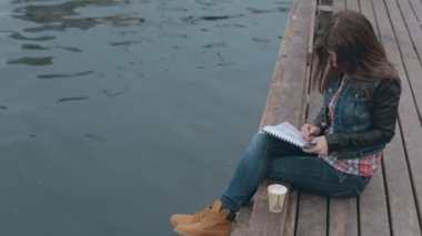 Cute girl sitting on a wooden pier near the sea and drawing — Stock Video