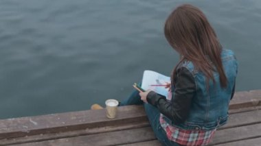 Charming girl sits on a wooden pier near the sea and drawing with colored pencils — Stock Video