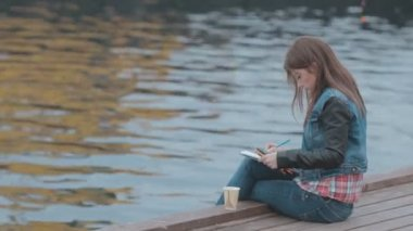 Creative girl drawing with colored pencils, then drinking coffee while sitting on a wooden pier near the sea — Stock Video