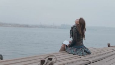 Romantic girl in skirt sitting on the pier near the sea and drawing — Stockvideo