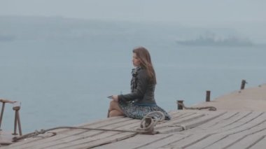 Romantic girl in skirt sitting on the pier near the sea and drawing, beside boat sailing — Stockvideo