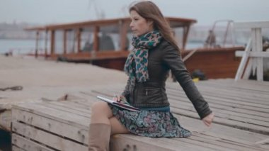Close up of a mysterious smiling girl in a skirt sitting on the pier near the sea and drawing — Stock Video