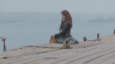Close up of a cute girl sitting on the dock looking at the sea, where the boat floats — Stockvideo