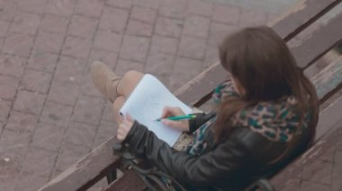 Romantic girl sitting on a bench and drawing pair of lovers in pencil, top view — Stock Video