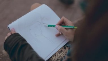 Close up of girl which drawing a picture of kissing couple on a bench — Vídeo de stock