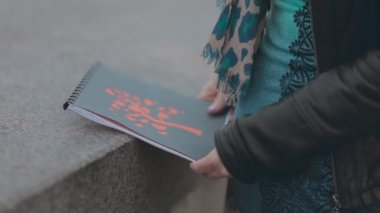 Close up of beautiful cover of album in the hands of girl — Stock Video