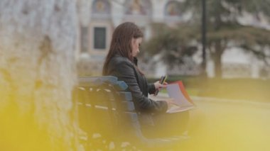 Beautiful brunette girl drawing in the album with bright pencils sitting on bench in park near the church — Stock Video
