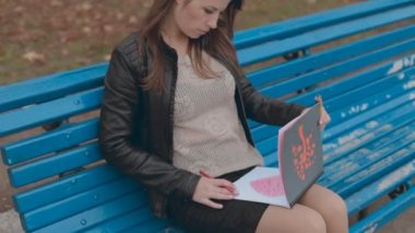 Absorbed in drawing girl sitting on a bench in autumn park — Stockvideo