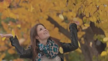 Lovely girl laughing under a tree from where yellow leaves falling — Stock Video