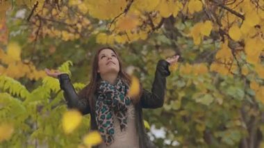 Cheerful girl standing under falling leaves and rejoices — Stock Video