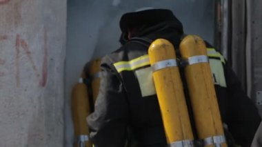 Firefighters in uniform and gas masks open the doors of the building full of foam — Stock Video
