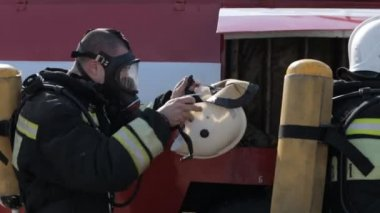 Firefighters wear gas masks and uniforms while standing by fire engine — Stock Video