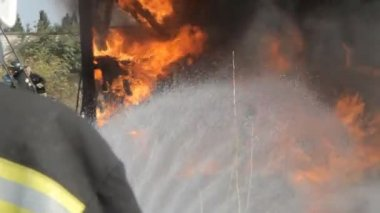 Firefighter extinguishes fire with a water jet from hose — Stockvideo