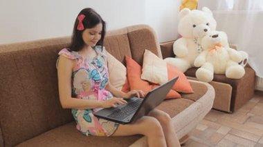 девушка с ноутбуком, сидя на диване — Стоковое видео