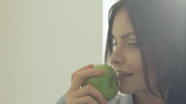Close-up of magnificent brunette standing in the kitchen in shirt with an apple in her hands and flirting on camera — Stock Video