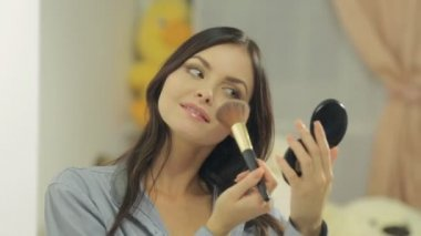 Attractive brunette powders her face with brush and looking in the mirror — Stock Video