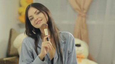 Seductive young woman with long hair powder her face with brush and winks at the camera — Αρχείο Βίντεο