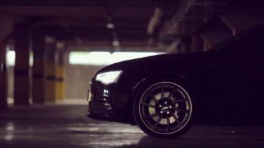 Black Audi leaves the parking lot with its lights on — Stock Video