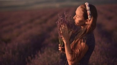 Dreamy girl in sundress standing in the middle of a blossoming field of lavender with a bouquet of lavender — Stock Video