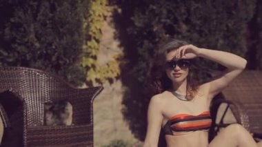 Beautiful girl in the points sits by pool — Vidéo
