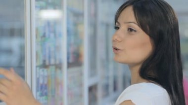 Young beautiful girl in drugstore — Stock Video